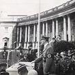Anschluss Österreichs an das Deutsche Reich 1938. Hitler am Stehpult am Heldenplatz, hinter ihm, tiefer stehend Militärs, zwei Fotografen bei der Arbeit. © VGA (E3/553)